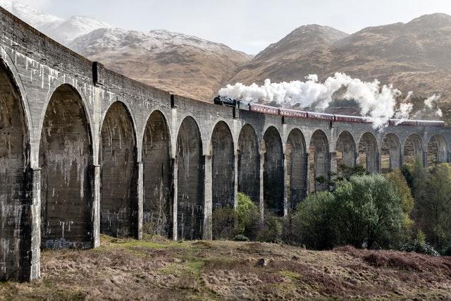 parní vlak s kouřícím komínem jede po mostě