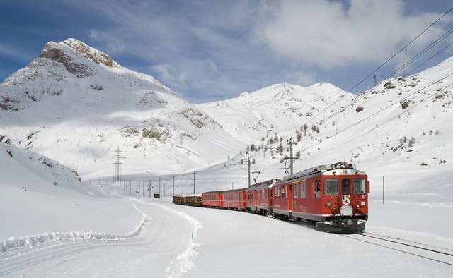 červená lokomotiva jede po kolejích v zimě na horách